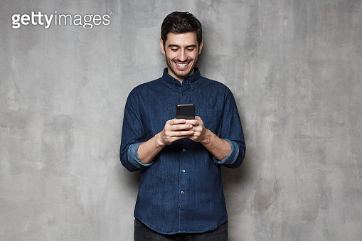 Young man smiling and laughing as he is browsing Internet or communicating via phone, isolated on gray textured wall