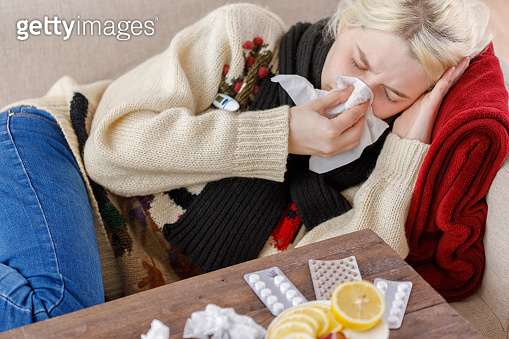 Girl in a sweater sneezes while sitting on a sofa. Colds and flu. The patient caught a cold, feeling sick and sneezing in a paper napkin. An unhealthy girl wiped her nose.