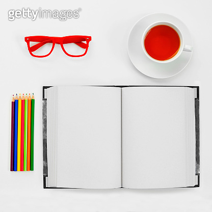 colored pencils, blank notebook, eyeglasses and cup of tea on a white table