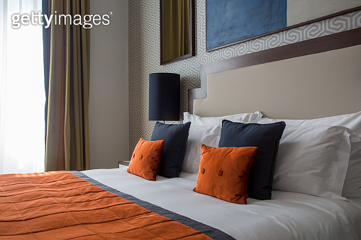 Arranged pillows on a king-size bed, orange, dark blue and white color scheme