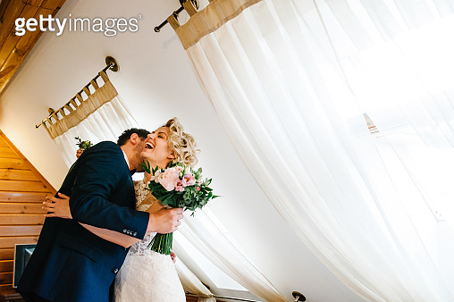 The groom in suit hugs bride in white dress are holding a beautiful wedding bouquet at home. Portrait of a beautiful young couple.