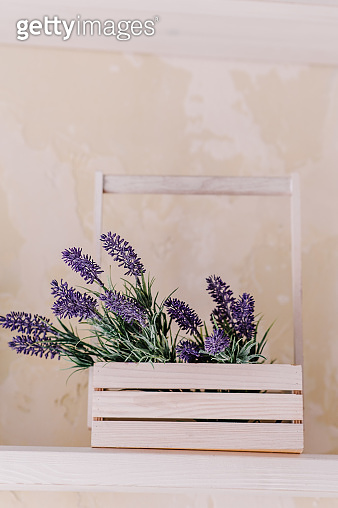 Bunch of lavender and greenery in wooden box vase on a white table on a vintage shelf over pastel wall. Chic provence interior decor for farm home style. Provence home decoration.