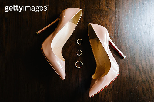 Wedding Gold rings and stylish elegant classic lacquered beige shoes on wooden background. Close up. Top view. Flat lay.