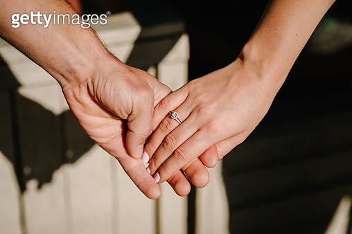 Man holding his girlfriend's hand. Man making a marriage proposal to his girlfriend - Happy engaged couple holding hands. Love, family, anniversary concept.