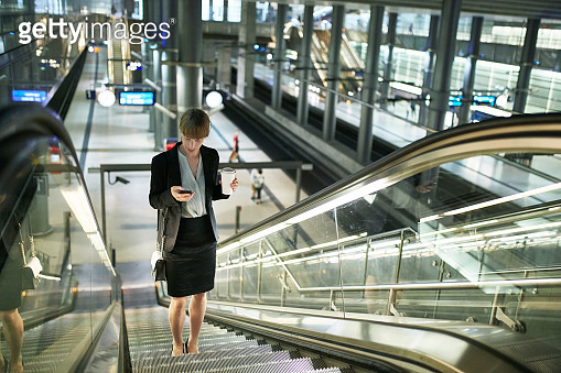 Berlin Businesswoman Moving Up on Escalator in Train Station