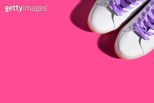 White sneakers with purple laces on bold pink