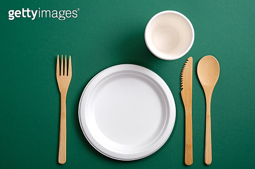 Eco friendly bamboo kitchenware with paper mug and plate on green background. Zero waste, plastic free concept. Sustainable lifestyle. Flat lay, top view.