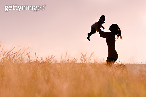 Mother playing with her baby outdoor, silhouette.