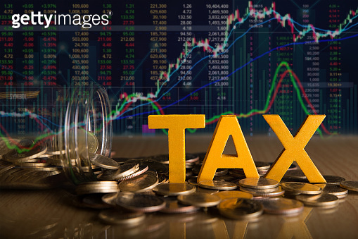 Tax Concept.Word tax put on coins and glass bottles with coins inside on black background.Stock market or forex trading graph and candlestick chart