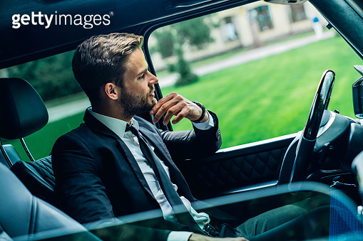 Sive view shot of mindfull handsome young man in full suit looking through the window while sitting in the car