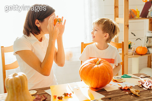 Happy Halloween. Young woman with her little son are preparing to Halloween on kitchen. Mother with son are having fun with pumpkins. Happy Halloween concept