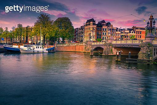 Dutch water canals with moored boats at sunset, Amsterdam, Netherlands