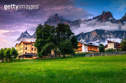 Village with houses and high mountains at sunset, Dolomites, Italy