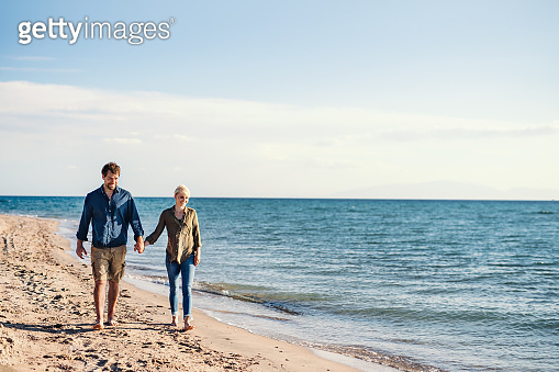 Young couple walking outdoors on beach, holding hands. Copy space.