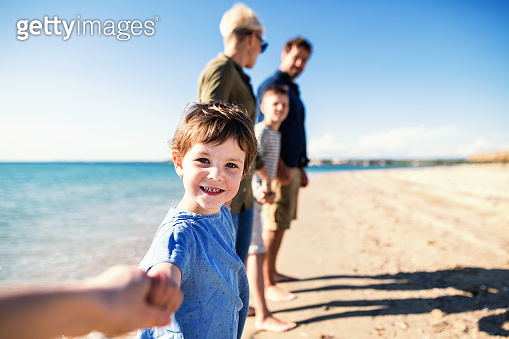 Young family with two small children standing outdoors on beach.