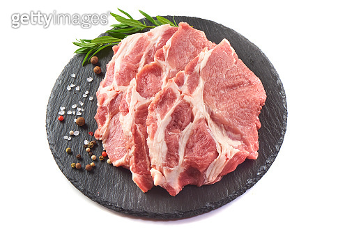 Sliced raw pork meat on stone plate, isolated on white background.