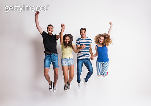 Portrait of joyful young group of friends jumping in a studio.