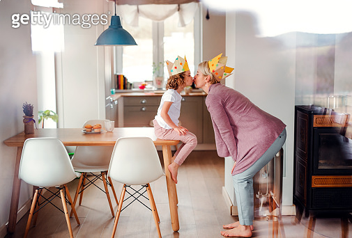 A portrait of small girl and mother with paper crown at home, kissing.