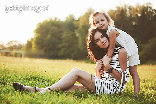 Happy mother and daughter hugging in a park in the sun on a bright summer background of herbs.