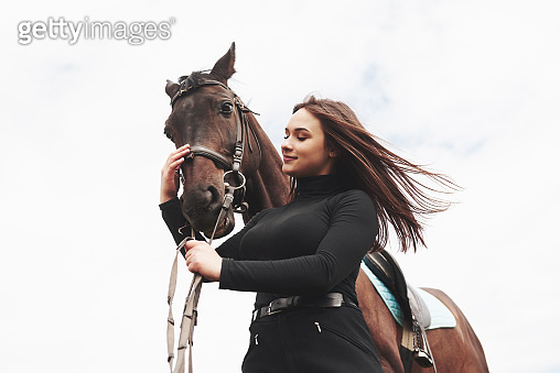 A happy girl communicates with her favorite horse. The girl loves animals andhorseback riding
