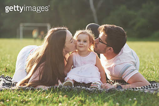 Mother and father spend time together happily. Little daughter plays with her parents outdoors during sunset