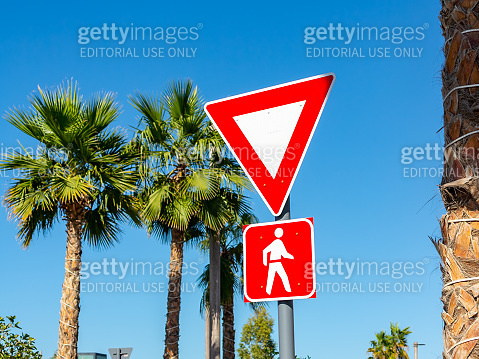 Dubai, United Arab Emirates - December 12, 2018: Yield To Pedestrians Sign in red frames against the blue sky and palm