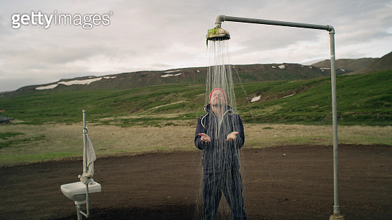 Outdoor shower in the middle of nowhere. Man taking fake bath