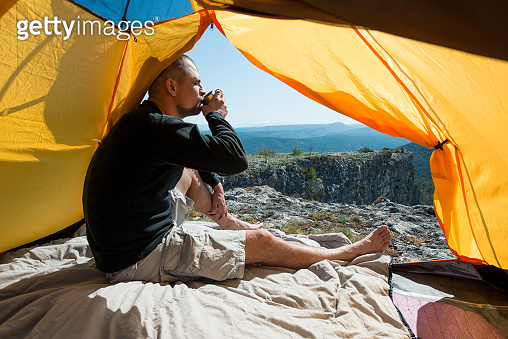 Man drinks from a mug in an camping outdoor