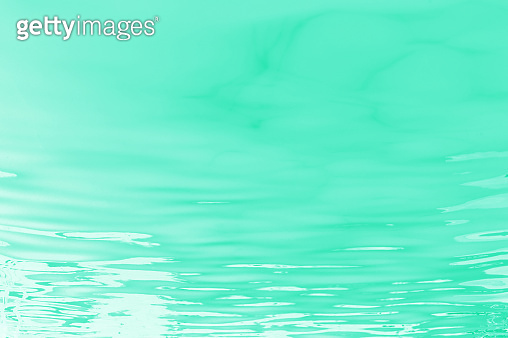 neo mint water of pool or sea with waves and sunlight glares at surface. abstract background