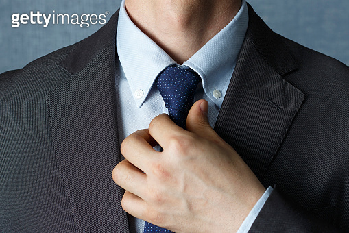 Man in suit straightens tie close-up, front view