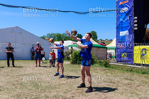 Young athletes performs exercises with dumbbells during ethno-rock festival Kozak Fest