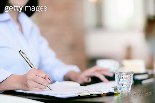 Cropped shot businesswoman writing with pen while sitting at office desk. Copy space.