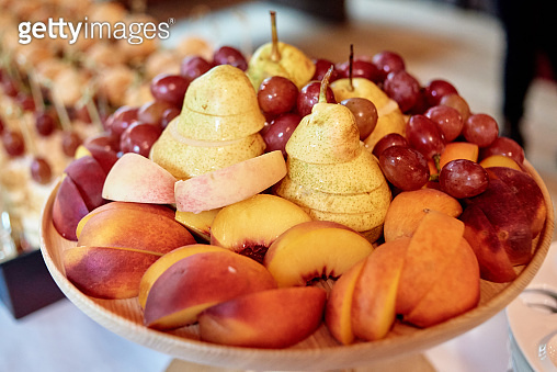 Plate with sliced fruits on servered buffet table at luxury wedding reception, copy space. Catering in restaurant. Food, party concept