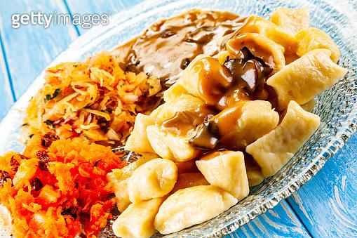 Potato noodles - dumplings on wooden background