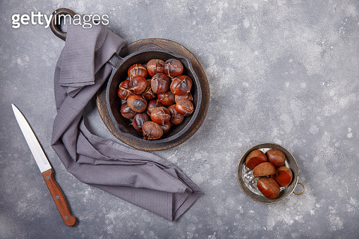 Roasted edible sweet chestnuts served in cast-iron skillet on gray background. Top view. Copy space.