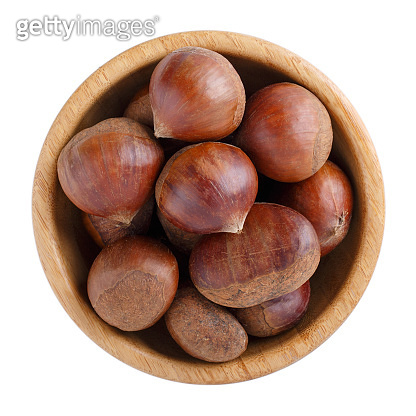 Fresh raw edible sweet chestnuts in wooden bowl isolated on white. Top view. Close-up.