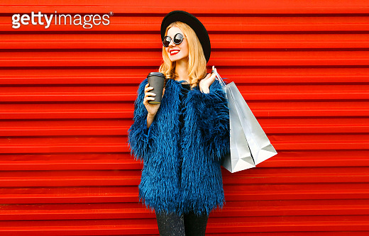 Portrait stylish smiling woman with coffee cup and shopping bags wearing blue faux fur coat, black round hat and sunglasses posing over red wall background