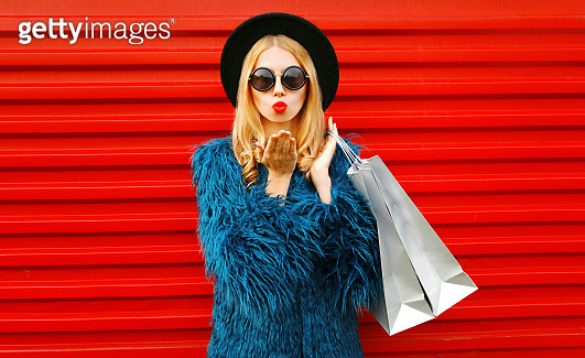Attractive young woman with shopping bags blowing red lips sending sweet air kiss, stylish female model wearing blue faux fur coat, round hat and sunglasses over red wall background