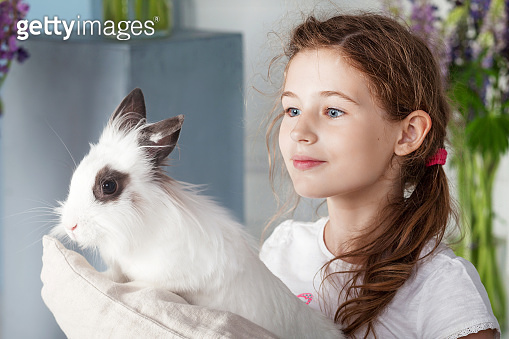 Little girl playing with real rabbit. Child and white bunny on Easter on flower background. Kids and pets play. Fun and friendship for animals and children.
