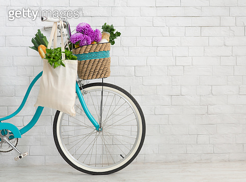 Bicycle with wildflowers and organic food over white bricks wall