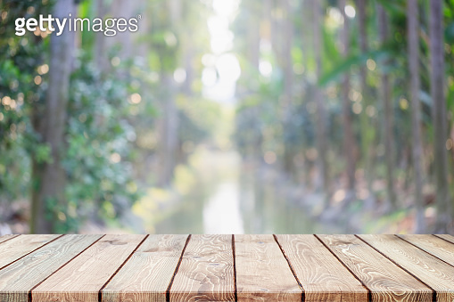 Empty wood table top and blurred green tree and fruit in agricultural farms. background - can used for display or montage your products.