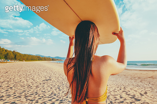 Women serfer with surfboard on beach background.