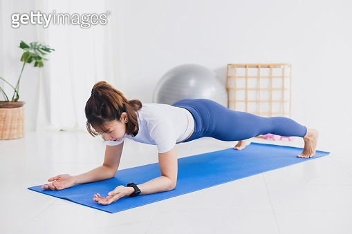 Asian beautiful woman exercise and play yoga at home.Concept of Exercise during the quarantine at home for preventing coronavirus and covid-19 infection.