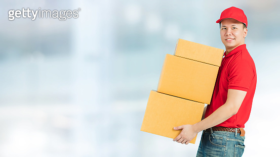 Asian happy delivery man wearing a red shirt carrying paper parcel boxes isolated on blur interior warehouse in the shopping mall background.Concept of Postal delivery service.