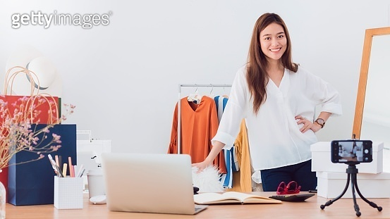 Beautiful asian woman blogger is showing and review product.In front of the smartphone camera to recording vlog video live streaming at home.Business online influencer on social media concept.