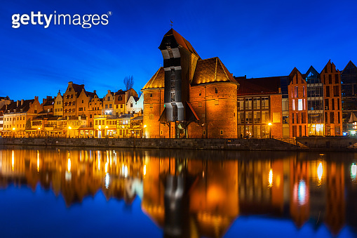 Old town in Gdansk with historical port crane over Motlawa river at night