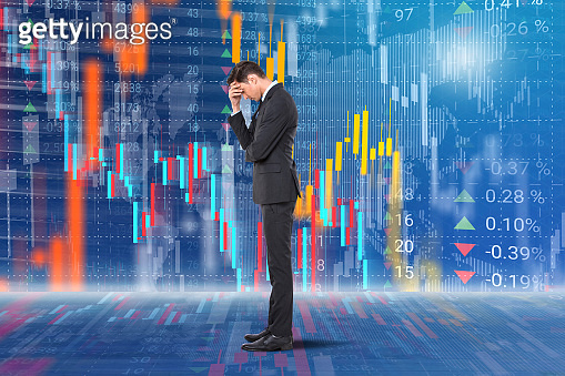 Frustrated businessman in front of stock market data