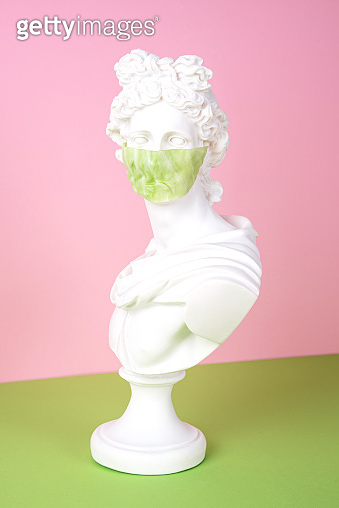 Gypsum statue with antiviral mask for protection against coronavirus, place for text.