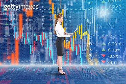 Businesswoman holding laptop in front of stock market data background