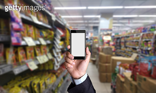Smart phone with blank screen held up in supermarket